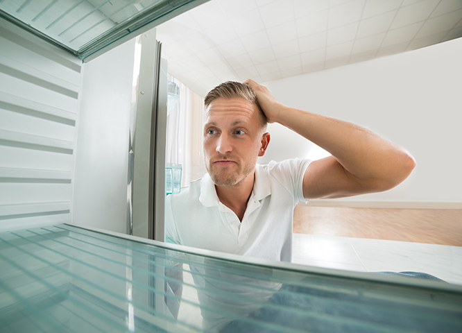 Portrait Of Hungry Man Looking In Empty Refrigerator In Kitchen